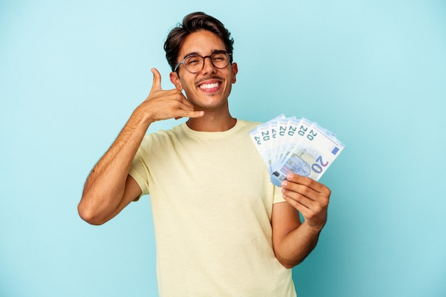 Young mixed race man holding bills isolated on blue background showing a mobile phone call gesture with fingers.