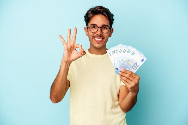 파란색 배경에 격리된 지폐를 들고 있는 젊은 혼혈 남성은 확인 제스처를 보여주며 명랑하고 자신감이 넘칩니다.
