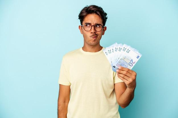 파란색 배경에 격리된 지폐를 들고 있는 혼혈 청년은 혼란스럽고 의심스럽고 확신이 서지 않습니다.