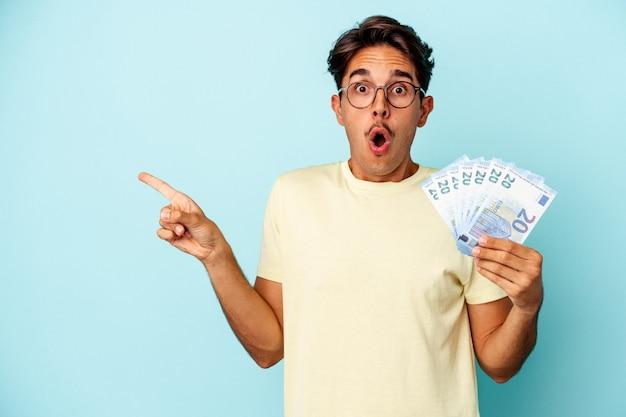 측면을 가리키는 파란색 배경에 고립 된 지폐를 들고 젊은 혼혈 남자
