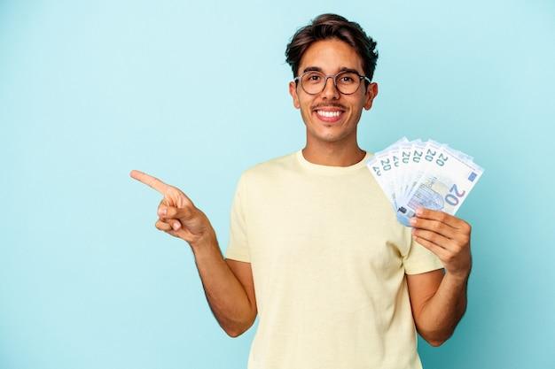 파란색 배경에 격리된 지폐를 들고 웃고 옆으로 가리키며 빈 공간에서 뭔가를 보여주는 젊은 혼혈 남자.
