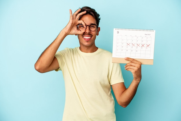 Young mixed race man holding calendar isolated on blue background excited keeping ok gesture on eye.