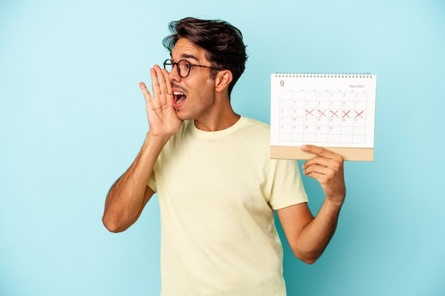 Young mixed race man holding calendar isolated on blue background shouting and holding palm near opened mouth.