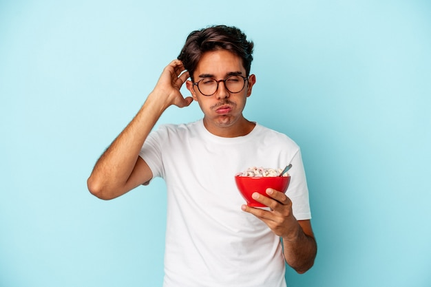 Young mixed race man holding cereals isolated on blue background being shocked, she has remembered important meeting.