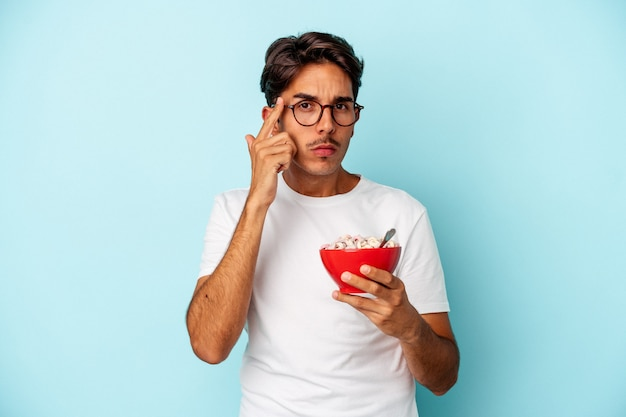 Young mixed race man holding cereals isolated on blue background pointing temple with finger, thinking, focused on a task.