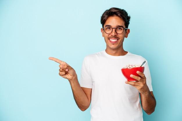 青い背景に分離されたシリアルを保持している若い混血の男は、笑顔で脇を指して、空白のスペースで何かを示しています。