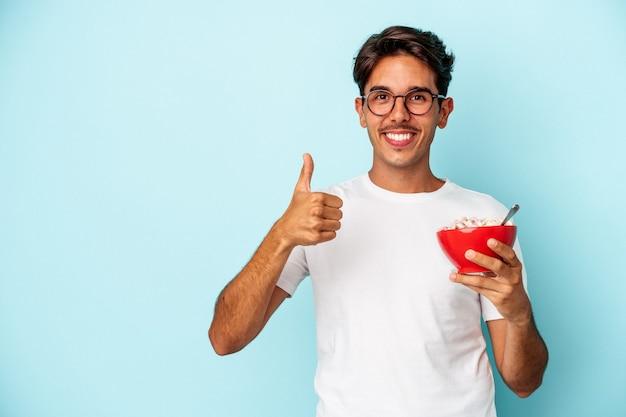 青い背景に分離されたシリアルを保持している若い混血の男笑顔と親指を上げる