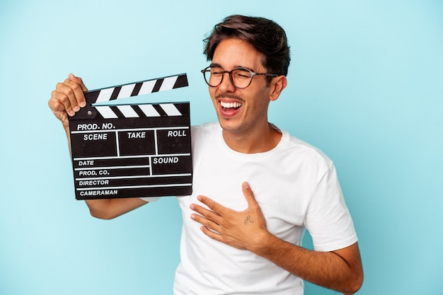 Young mixed race man holding clapperboard isolated on blue background laughing and having fun.