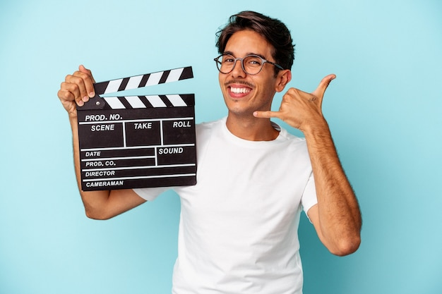 Young mixed race man holding clapperboard isolated on blue background showing a mobile phone call gesture with fingers.
