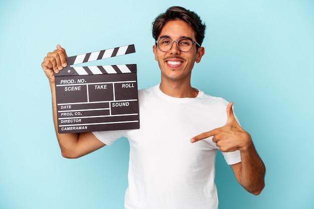 Молодой человек смешанной расы, держащий с 'хлопушкой', изолированный на синем фоне, человек, указывающий рукой на пространство для копирования рубашки, гордый и уверенный