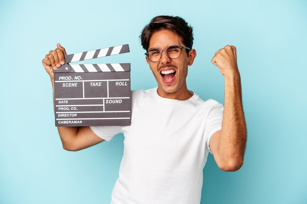 Молодой человек смешанной расы, держащий с 'хлопушкой', изолированные на синем фоне, поднимая кулак после победы, концепции победителя.