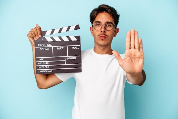 파란색 배경에 격리된 클래퍼보드를 들고 있는 젊은 혼혈 남성이 정지 신호를 보여주는 뻗은 손으로 서서 당신을 막습니다.