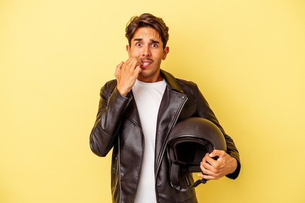 Молодой человек смешанной расы, держащий шлем, изолированный на желтом фоне, кусает ногти, нервничает и очень тревожится.