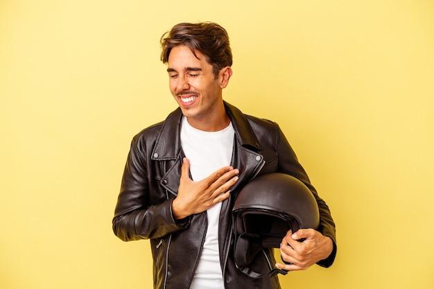 Молодой смешанной расы человек, держащий шлем, изолированные на желтом фоне, смеясь и весело.
