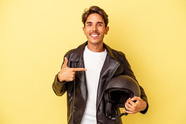 Молодой человек смешанной расы, держащий шлем, изолированный на желтом фоне, человек, указывающий рукой на пространство для копирования рубашки, гордый и уверенный