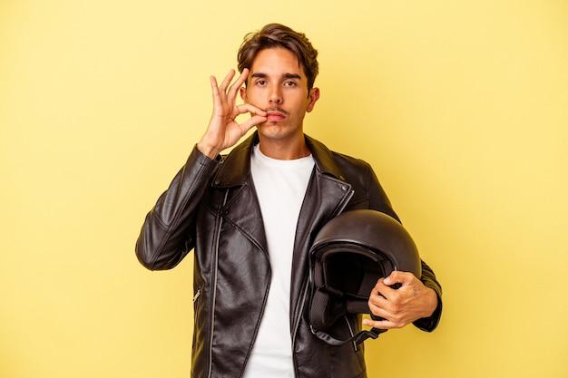 Молодой человек смешанной расы, держащий шлем, изолированный на желтом фоне с пальцами на губах, сохраняя в секрете.
