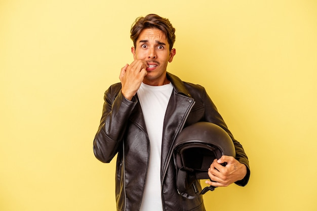 Young mixed race man holding helmet isolated on yellow background biting fingernails, nervous and very anxious.