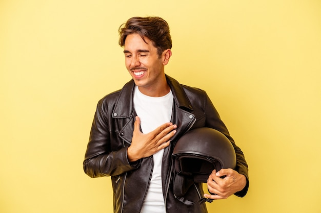 Young mixed race man holding helmet isolated on yellow background laughing and having fun.