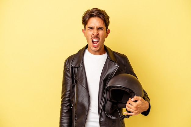 Young mixed race man holding helmet isolated on yellow background screaming very angry and aggressive.