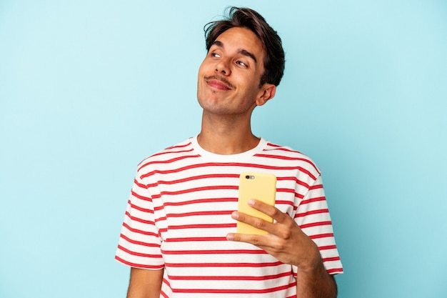 Young mixed race man holding mobile phone isolated on blue background dreaming of achieving goals and purposes
