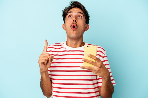 Young mixed race man holding mobile phone isolated on blue background pointing upside with opened mouth.