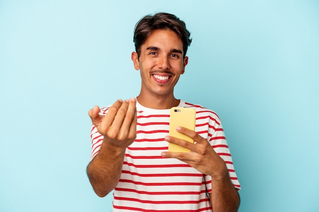 Young mixed race man holding mobile phone isolated on blue background pointing with finger at you as if inviting come closer.