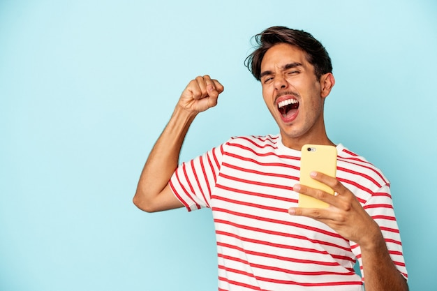 Young mixed race man holding mobile phone isolated on blue background raising fist after a victory, winner concept.