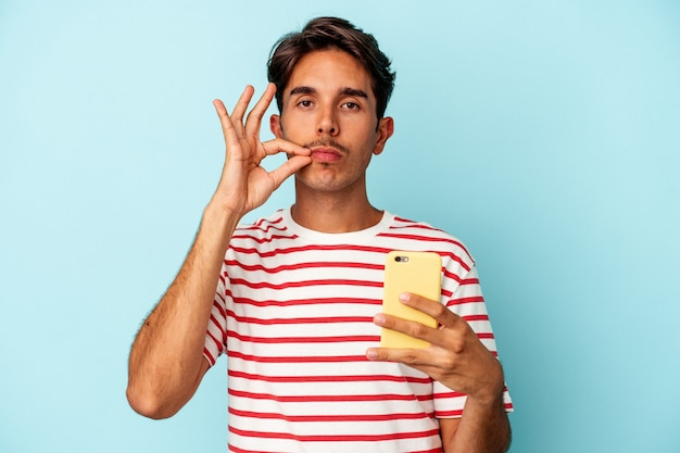 Young mixed race man holding mobile phone isolated on blue background with fingers on lips keeping a secret.