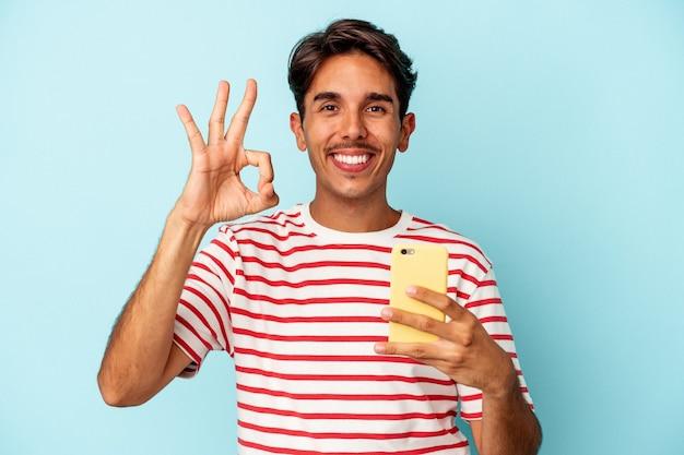 青い背景に分離された携帯電話を持っている若い混血の男は、陽気で自信を持って大丈夫なジェスチャーを示しています。