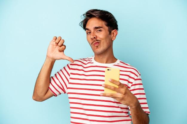 青い背景で隔離の携帯電話を保持している若い混血の男は、誇りと自信を持って、従うべき例を感じます。