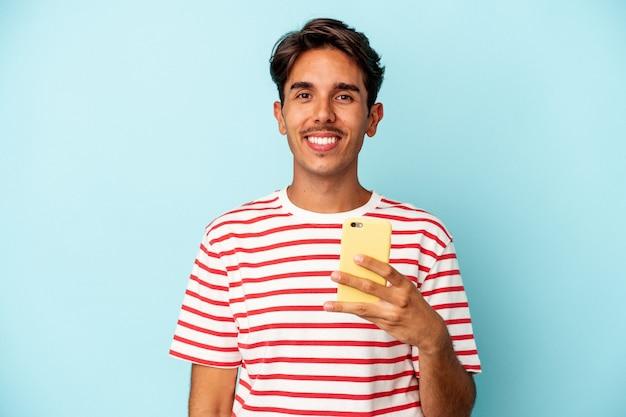 青い背景で隔離の携帯電話を保持している若い混血の男は幸せ、笑顔、陽気な。