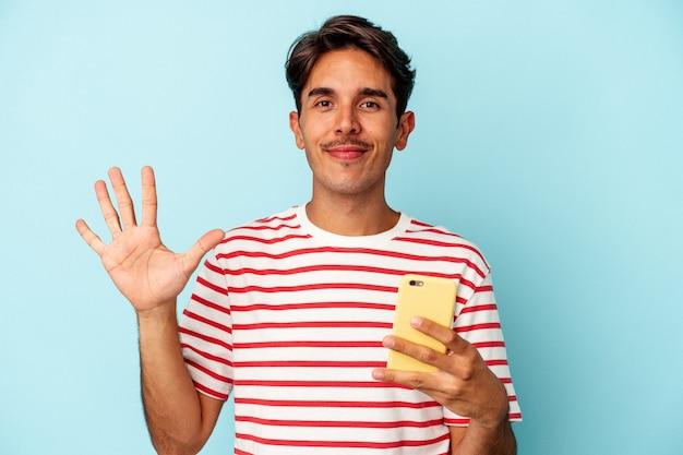 青い背景に分離された携帯電話を持っている若い混血の男は、指で5番を示して陽気に笑っています。
