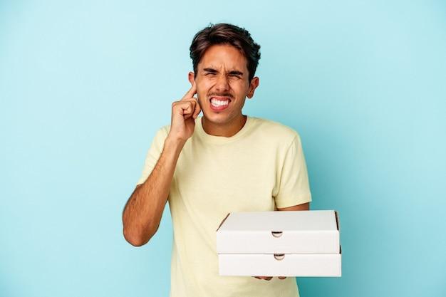 手で耳を覆う青い背景に分離されたピザを保持している若い混血の男。