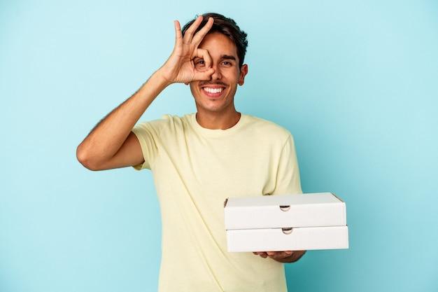 青い背景に分離されたピザを保持している若い混血の男は、目に大丈夫なジェスチャーを維持して興奮しました。