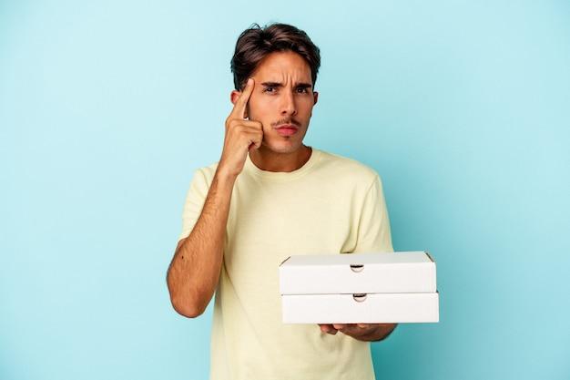 青い背景に分離されたピザを持っている若い混血の男は、指で寺院を指して、考えて、タスクに焦点を当てた。