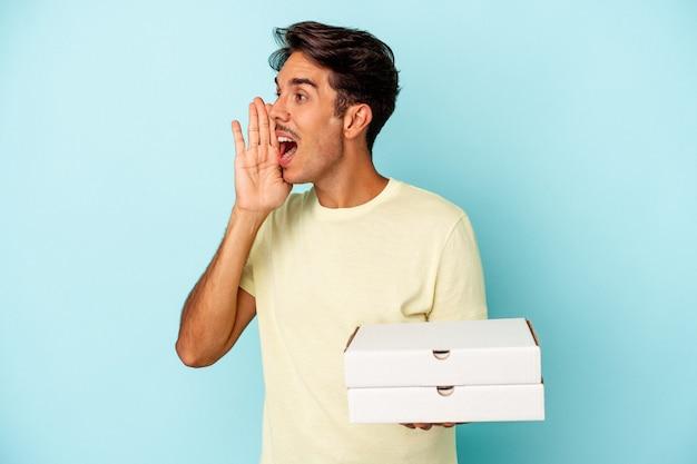 青い背景に分離されたピザを持って叫び、開いた口の近くで手のひらを保持している若い混血の男。