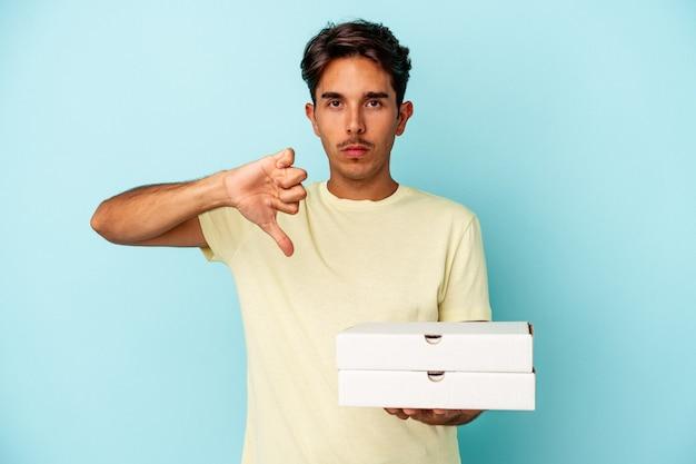 嫌いなジェスチャーを示す青い背景に分離されたピザを持っている若い混血の男は、親指を下に向けます。不一致の概念。