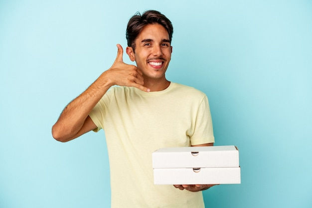 指で携帯電話の呼び出しジェスチャーを示す青い背景で隔離のピザを保持している若い混血の男。