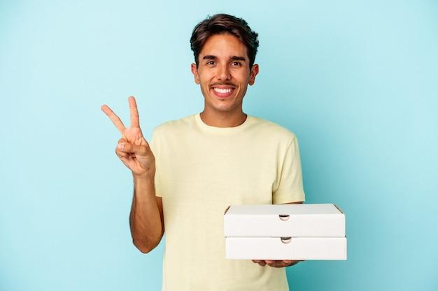 指で2番目を示す青い背景で隔離のピザを保持している若い混血の男。