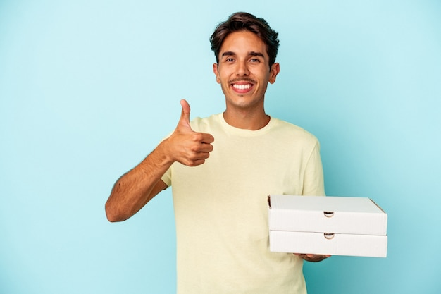 青い背景に分離されたピザを持って笑顔と親指を上げる若い混血の男