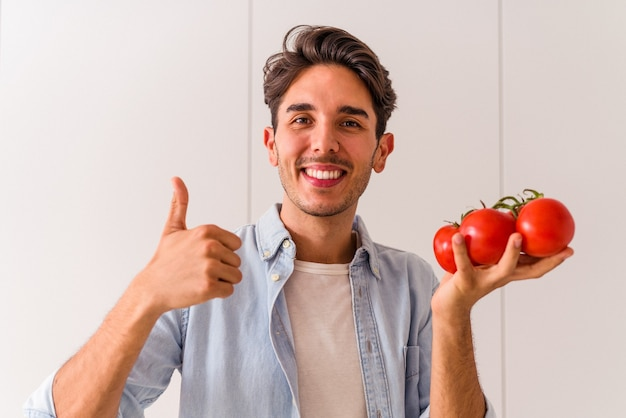 Young mixed race man holding tomatoes in his kitchen
