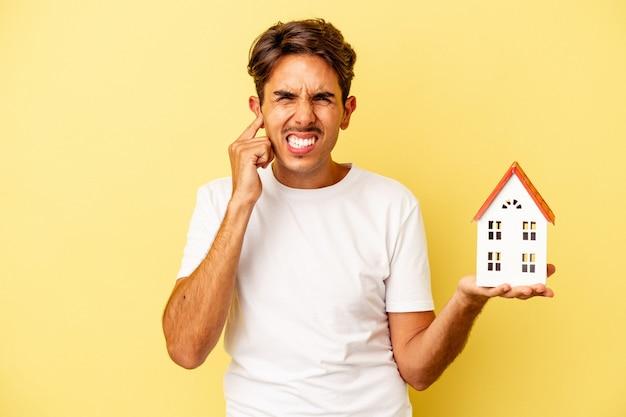 手で耳を覆う黄色の背景に分離されたおもちゃの家を保持している若い混血の人。