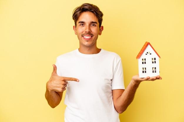 Молодой человек смешанной расы, держащий игрушечный домик, изолированный на желтом фоне, человек, указывая рукой на пространство для копирования рубашки, гордый и уверенный