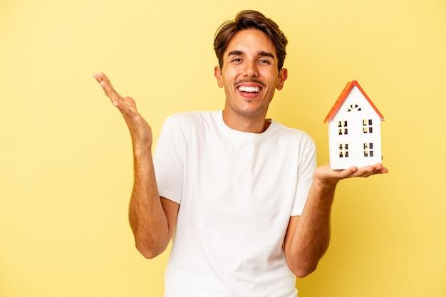 Молодой человек смешанной расы держит игрушечный домик на желтом фоне, получая приятный сюрприз, возбужденный и поднимающий руки.