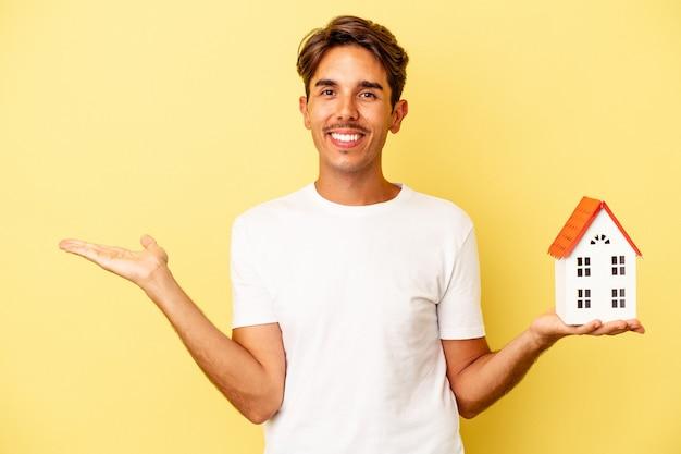 Молодой человек смешанной расы, держащий игрушечный домик, изолированный на желтом фоне, показывает пространство для копии на ладони и держит другую руку на талии.