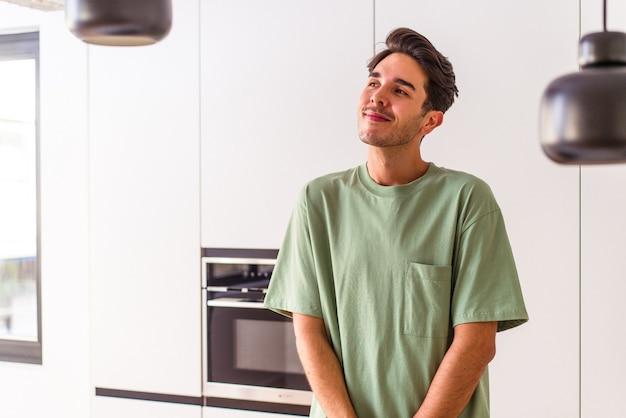 目標と目的を達成することを夢見ている彼の台所の若い混血の男