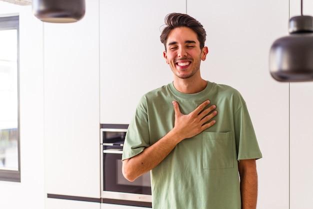 Молодой человек смешанной расы на своей кухне громко смеется, держа руку на груди.