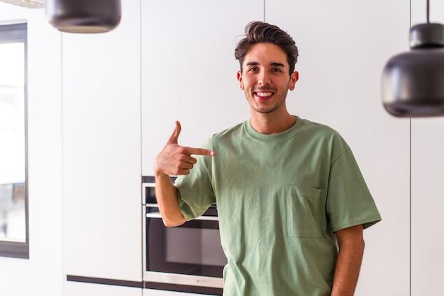 Молодой человек смешанной расы на своей кухне человек, гордый и уверенный в себе, указывая рукой на место для копирования рубашки