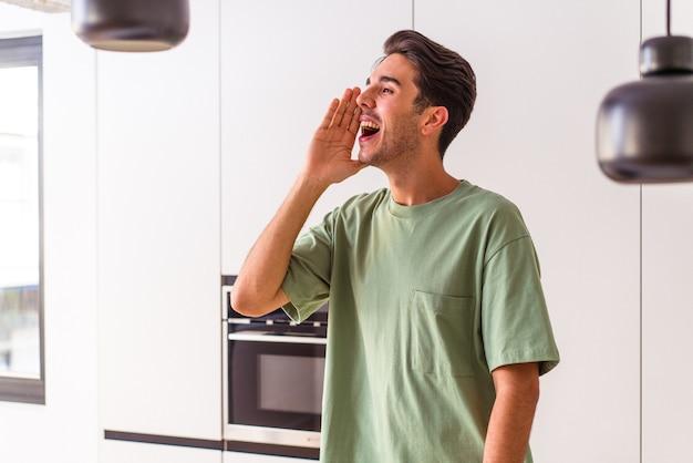 Молодой человек смешанной расы в своей кухне кричит и держит ладонь возле открытого рта.