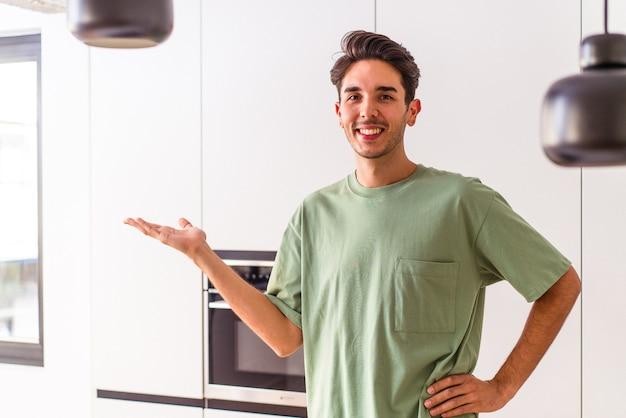 Молодой человек смешанной расы в своей кухне показывает место для копии на ладони и держит другую руку на талии.